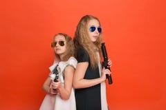 Deux filles dans des robes militaires avec des bras à disposition et des lunettes de soleil o Photos stock