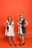 Deux filles dans des robes militaires avec des bras à disposition et des lunettes de soleil o Photo libre de droits