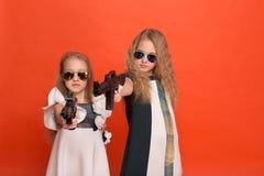 Deux filles dans des robes militaires avec des bras à disposition et des lunettes de soleil o Images libres de droits
