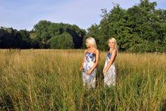 Deux filles dans l'herbe près de la forêt Image libre de droits