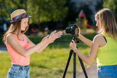 Deux filles dans la nature Enregistrez un message visuel sur l'Internet Dans la ville après école Appareil-photo avec le trépied  Images libres de droits