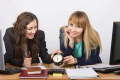 Deux filles dans le bureau attendant heureusement la fin du jour ouvrable Photo stock