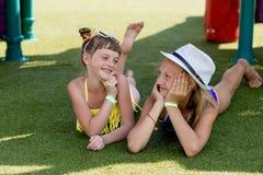 Deux filles dans le maillot de bain ont l'amusement sur l'herbe par la piscine Image libre de droits