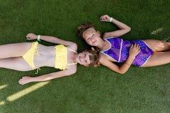 Deux filles dans le maillot de bain ont l'amusement sur l'herbe par la piscine Photo libre de droits