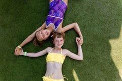 Deux filles dans le maillot de bain ont l'amusement sur l'herbe par la piscine photo stock
