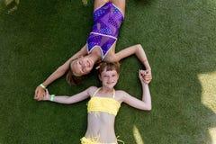 Deux filles dans le maillot de bain ont l'amusement sur l'herbe par la piscine images stock