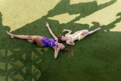 Deux filles dans le maillot de bain ont l'amusement sur l'herbe par la piscine photographie stock
