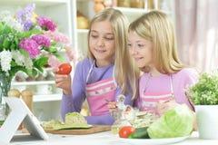 Deux filles dans les tabliers préparant la salade fraîche images libres de droits