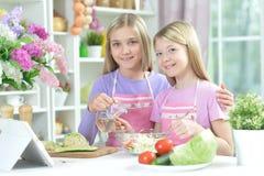Deux filles dans les tabliers préparant la salade fraîche images stock