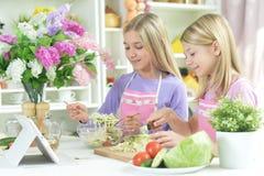 Deux filles dans les tabliers préparant la salade fraîche image libre de droits