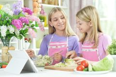 Deux filles dans les tabliers roses préparant la salade fraîche photographie stock