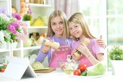 Deux filles dans les tabliers roses préparant la salade fraîche images stock