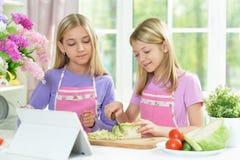 Deux filles dans les tabliers roses préparant la salade photographie stock