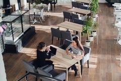 Deux filles dans un café, souriant, bavardant, café potable Image libre de droits