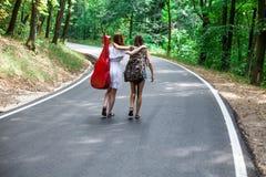 Deux filles dans une route faisant de l'auto-stop avec le sac à dos et la guitare Photo stock