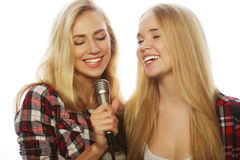 Deux filles de beauté avec un microphone chantant et ayant l'amusement Image stock