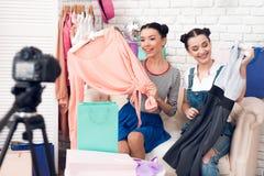 Deux filles de blogger de mode tirent la robe colorée des sacs colorés à l'appareil-photo image libre de droits