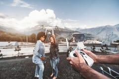 Deux filles de différentes courses, de contrôleur à distance et du bourdon Photo libre de droits