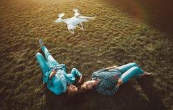 Deux filles de différentes courses sur l'herbe et le bourdon Photographie stock