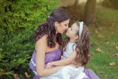 Deux filles de femme d'yeux bleus de brune de châtaigne d'amies de soeurs posant ensemble la soirée de jour ensoleillé d'été se s Photos stock