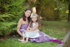 Deux filles de femme d'yeux bleus de brune de châtaigne d'amies de soeurs posant ensemble la soirée de jour ensoleillé d'été se s Photographie stock libre de droits