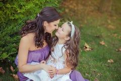 Deux filles de femme d'yeux bleus de brune de châtaigne d'amies de soeurs posant ensemble la soirée de jour ensoleillé d'été se s Photos libres de droits