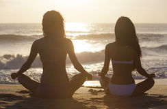 Deux filles de femmes de bikini reposant la plage de lever de soleil de coucher du soleil Images stock
