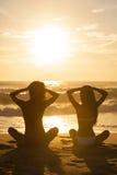 Deux filles de femmes reposant la plage de bikini de coucher du soleil de lever de soleil images stock