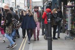 Deux filles de hippie se sont habillées dans le style frais de Londonien marchant dans la ruelle de brique, une rue populaire par Images stock
