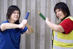 Deux filles de l'adolescence asiatiques avec de grands crayons Image stock