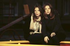 Deux filles de l'adolescence de mode heureuse sur le terrain de jeu pendant la nuit Photo libre de droits