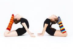 Deux filles de l'adolescence flexibles faisant la gymnastique s'exerce sur un blanc Photographie stock
