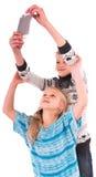 Deux filles de l'adolescence font le selfie sur un fond blanc Photo libre de droits