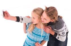 Deux filles de l'adolescence font le selfie sur un fond blanc Photographie stock libre de droits