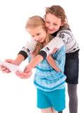 Deux filles de l'adolescence font le selfie sur un fond blanc Image stock