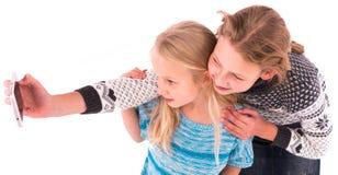 Deux filles de l'adolescence font le selfie sur un fond blanc Photo stock
