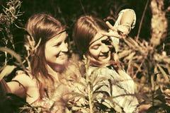 Deux filles de l'adolescence heureuses marchant dans la forêt d'été Images libres de droits