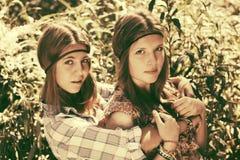 Deux filles de l'adolescence heureuses marchant dans la forêt d'été Photos stock