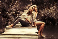 Deux filles de l'adolescence heureuses s'asseyant sur le pont en bois dans la forêt d'été Photographie stock
