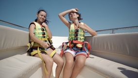 Deux filles de l'adolescence heureuses utilisant des ceintures de sécurité sur une danse de bateau Images libres de droits