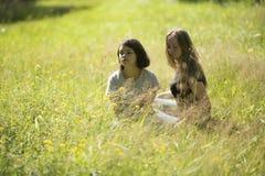 Deux filles de l'adolescence mignonnes s'asseyent sur le champ dans l'herbe nature Photos libres de droits
