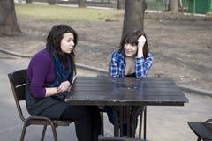 Deux filles de l'adolescence s'asseyant en café de rue Photographie stock libre de droits
