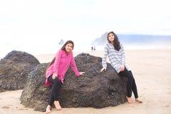 Deux filles de l'adolescence s'asseyant sur la grande roche sur la plage Image stock
