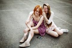Deux filles de l'adolescence s'asseyant sur le terrain de jeu Photographie stock libre de droits