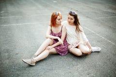 Deux filles de l'adolescence s'asseyant sur le terrain de jeu Photographie stock