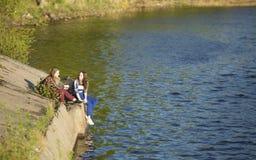 Deux filles de l'adolescence s'asseyant sur un pilier près de l'eau nature Image stock