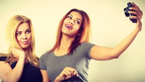 Deux filles de modèles prenant la photo d'individu avec l'appareil-photo Photo stock