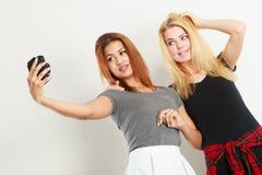 Deux filles de modèles prenant la photo d'individu avec l'appareil-photo Image libre de droits