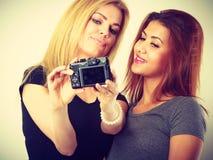 Deux filles de modèles prenant la photo d'individu avec l'appareil-photo Image stock