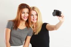 Deux filles de modèles prenant la photo d'individu avec l'appareil-photo Photos stock